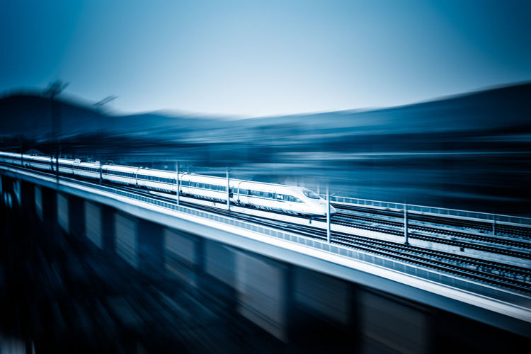 Blurred motion of train against clear blue sky