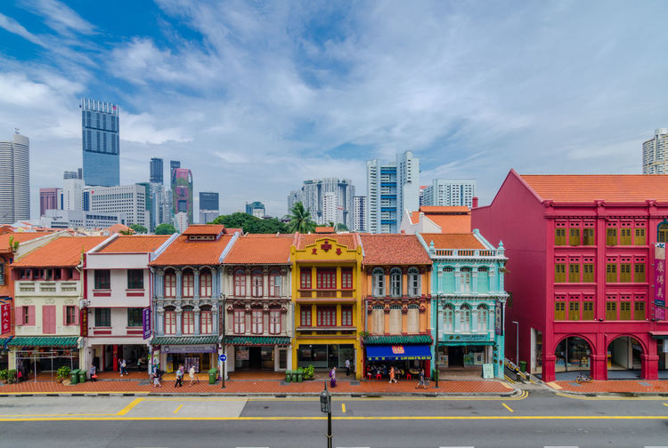 Road By Colorful Buildings Against Sky In City