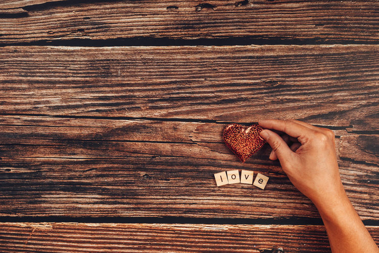 Directly above shot of woman hand on wooden table