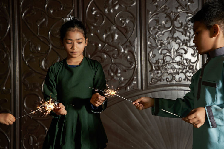 Portrait of malay girl  with traditional clothing playing fireworks sparkler