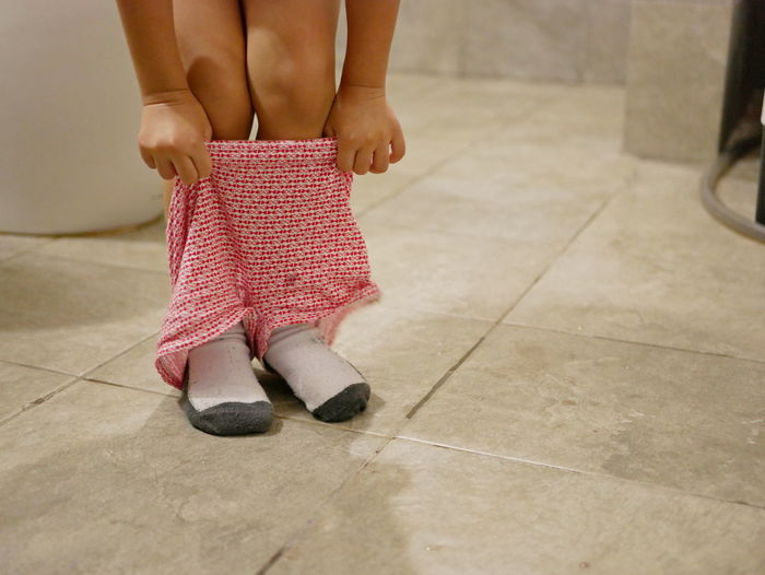 Selective focus of little baby's short pants being pulled up by herself after the baby finished using a toilet - potty trainning Toilet Bowl Toilet Baby Girl Asian  Toddler  Young Litle Kid Child Female Training Potty At Home Successfully By Herself Standing Pulling Putting On Shorts Pants Routine Finished Habit At Home Restroom