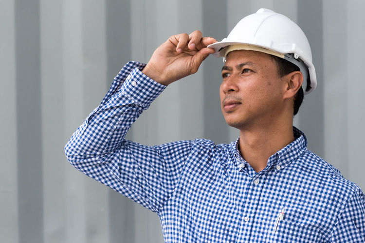 Architect Wearing Hardhat At Construction Site