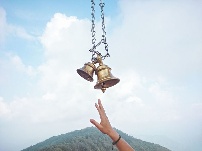 Cropped Hand Of Woman Reaching Bells Against Sky