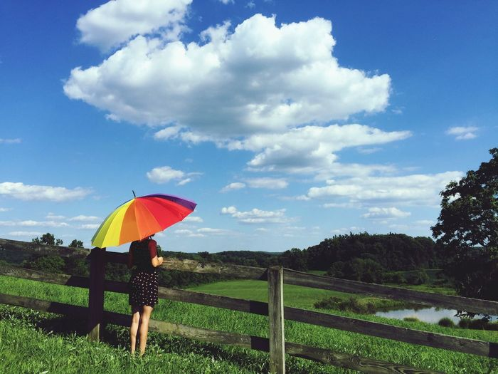 Rear view of woman holding multi colored umbrella on grassy landscape against cloudy sky