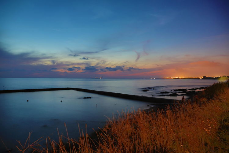EyeEmNewHere Beauty In Nature Cloud - Sky Grass Horizon Horizon Over Water Idyllic Nature Nautical Vessel No People Non-urban Scene Orange Color Outdoors Plant Reflection Scenics - Nature Sea Sky Sunset Tranquil Scene Tranquility Water