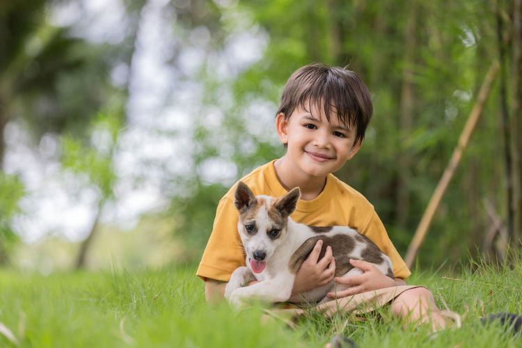 Boy sitting at park with dog