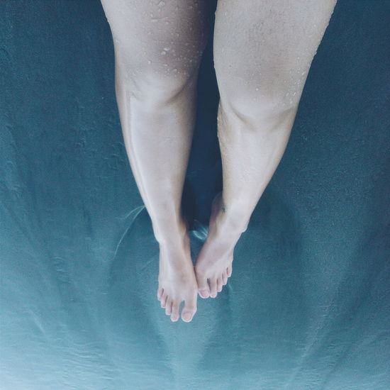 High Angle View Of Woman Legs On Sea Water