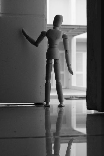 Woden mannequin standing behind the door, looking away