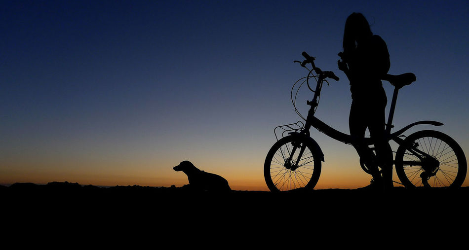 Silhouette of person riding bicycle against sky during sunset
