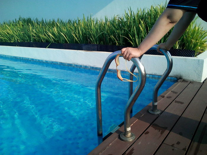 Cropped hands of person holding swimming goggles on ladder of pool