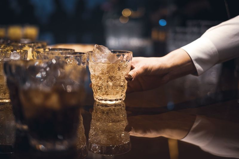 Cropped hand holding drinking glass on table