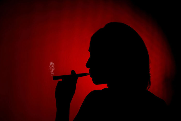 Silhouette of a girl smoking an ecig Silhouette Red Cigarette  Smoking Issues Social Issues Indoors  One Person Holding Smoking - Activity Portrait Bad Habit Studio Shot Red Background Vaping Vapingcommunity Ecig Ecigarette Smoke Vapor
