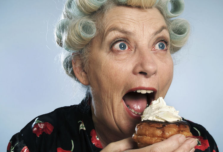 Close-up portrait of woman eating food over white background