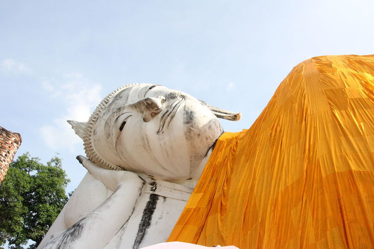Low angle view of reclining buddha statue against sky