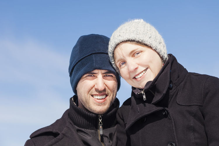 Portrait of smiling couple standing against sky during winter