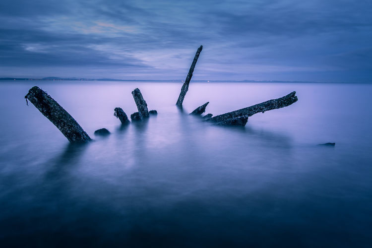 Driftwood In Sea Against Cloudy Sky During Dusk