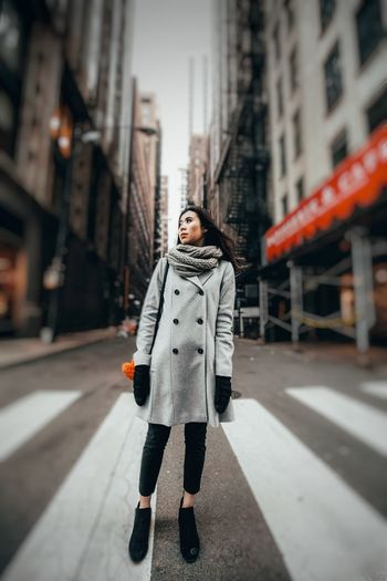 Full length of young woman standing on city street