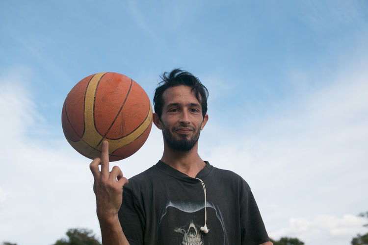 Portrait of young man with basketball against sky