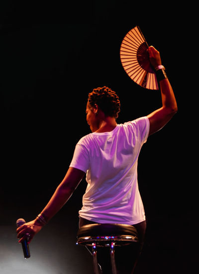 Young man with arms raised against black background