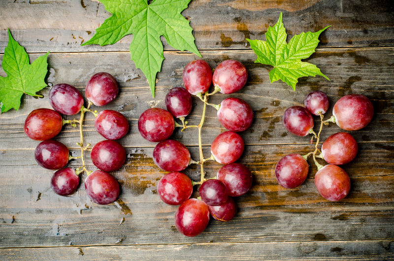 Directly Above Shot Of Red Grapes On Wet Wooden Table