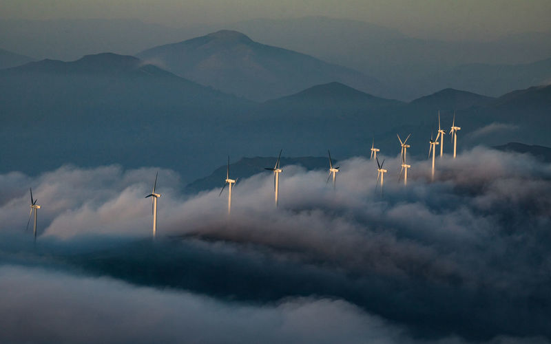 High Angle View Of Windmills Against Silhouette Mountains During Foggy Weather