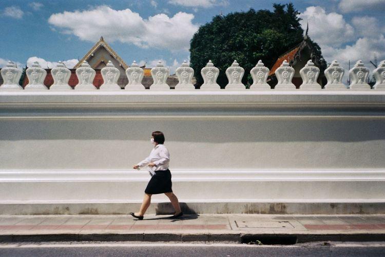 Full length of man walking against sky in city