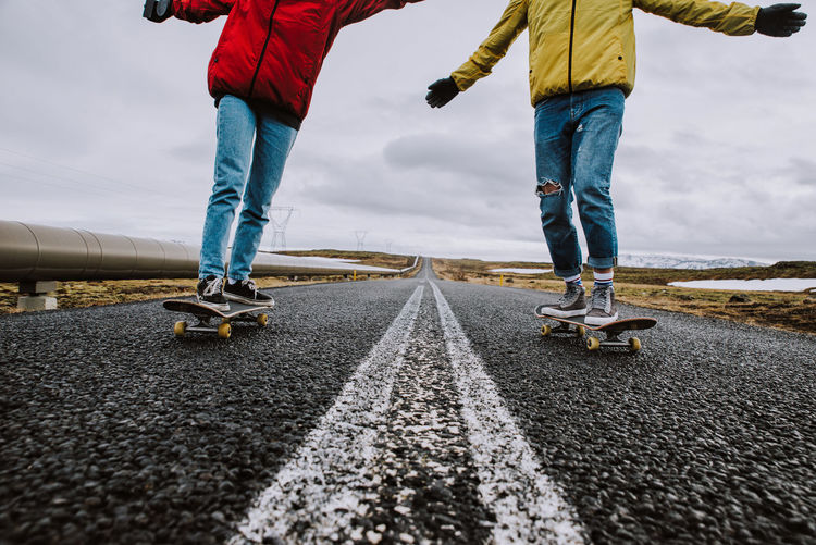 Lows section of couple skateboarding on road against sky