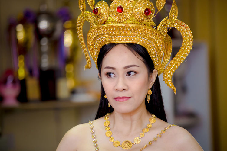 Mature Woman Wearing Golden Crown And Jewelries Looking Away At Home