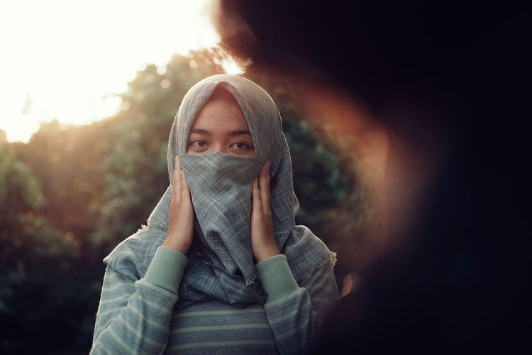 Portrait of young woman covering face with scarf