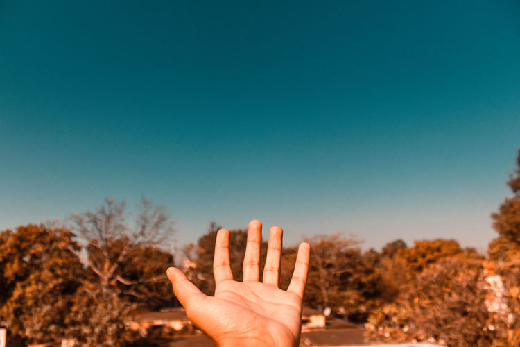 Cropped hand gesturing against clear blue sky