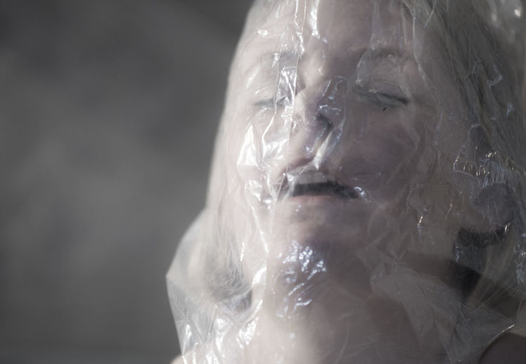 Close-up of woman with plastic bag on face
