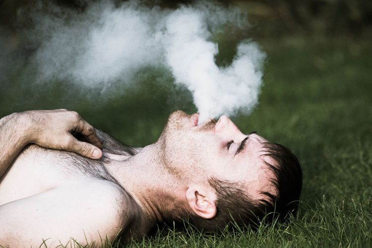 Shirtless man exhaling smoke while lying on field