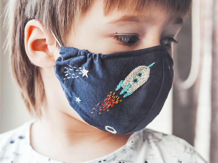 Boy with handmade protective mask on face. embroidered space theme. quarantine coronavirus covid19.