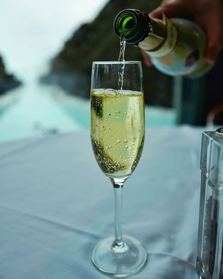 Cropped Image Of Hand Pouring Champagne In Flute On Table At Restaurant