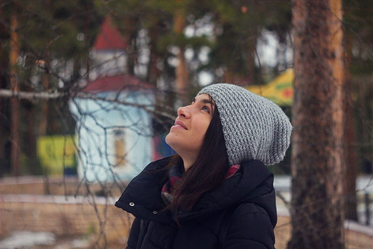 Close-up of smiling young woman looking up in park during winter