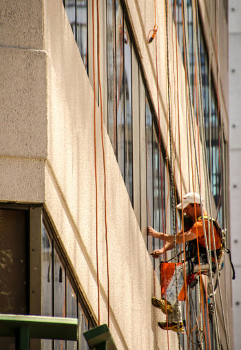 Low angle view of worker washing windows on building