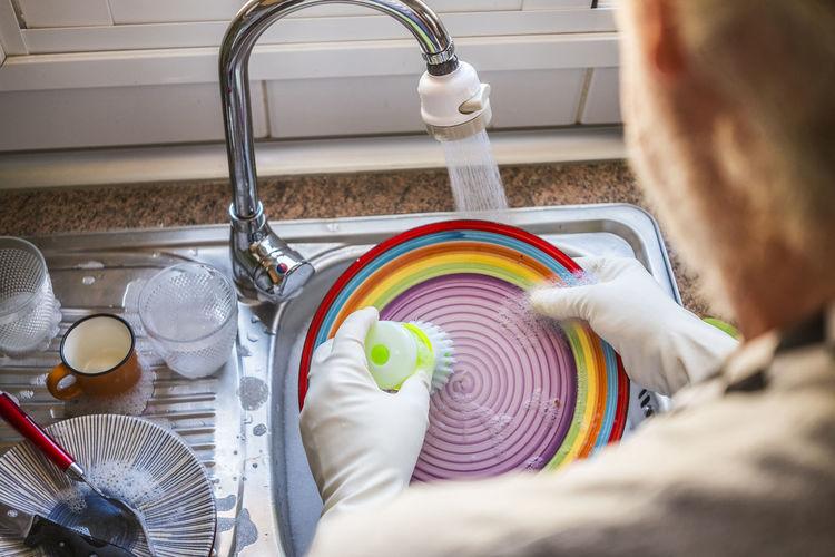 High angle view senior man washing dish at kitchen