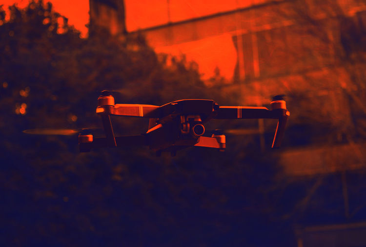 Close-up of drone in city during sunset