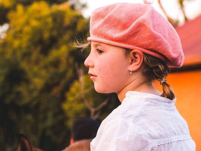 Close-up of thoughtful girl wearing flat cap against trees
