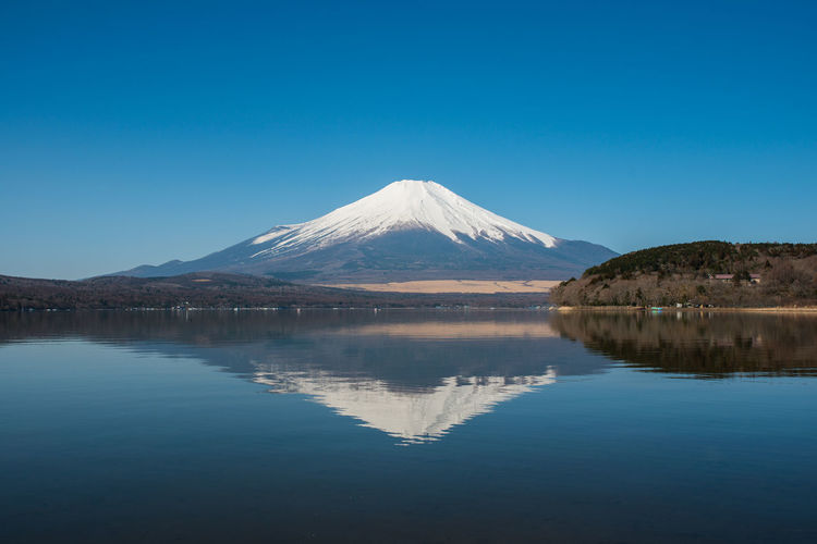 Beauty In Nature Blue Clear Sky Copy Space Fuji Fuji San Idyllic Lake Mountain Mountain Peak Mountain Range Nature No People Non-urban Scene Outdoors Reflection Scenics - Nature Sky Snowcapped Mountain Tranquil Scene Tranquility Travel Destinations Volcano Water Waterfront