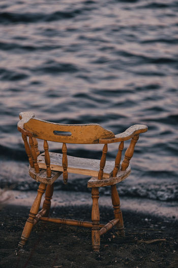 Wooden chair on sandy beach.