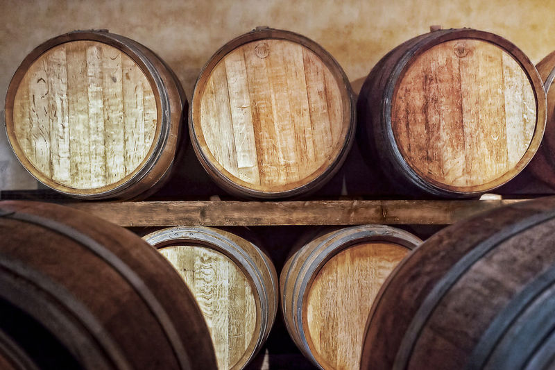 Oak barrels for wine fermentation. Oak barrels in a cellar, where the wine is aged after fermentation. Aging Process Barrel Cellar Day Food And Drink In A Row Indoors  Keg No People Oak Storage Tank Wine Wine Cask Wine Cellar Wineglass Winemaking Winery Winery View Wood - Material