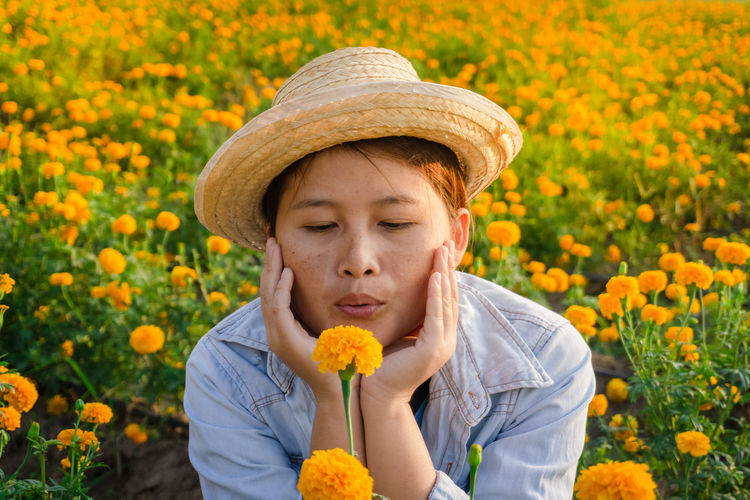 Marigold Portrait Flower Marigold Flower Farmer Selective Focus Lifestyles Outdoors Nature Plant Leisure Activity Care Check Flowering Plant Freshness Hat One Person Front View Yellow Headshot Beauty In Nature Real People Fragility Child Vulnerability  Childhood Clothing Flower Head Human Face
