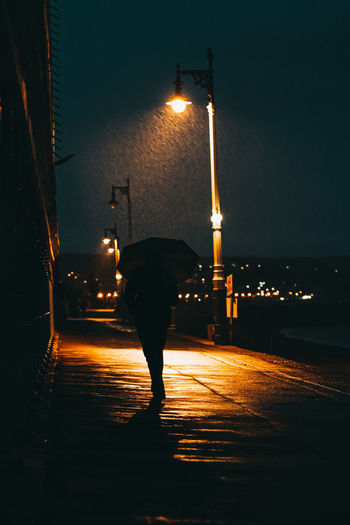 Rear view of silhouette man walking on illuminated street at night