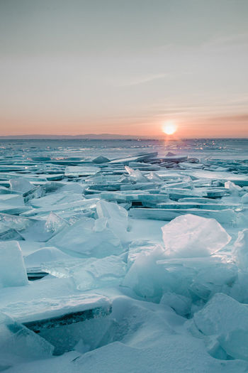 Scenic view of frozen sea against sky during sunset
