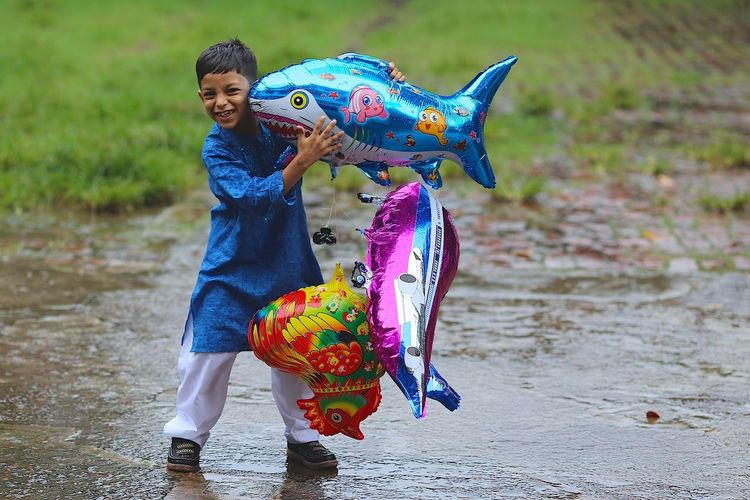 Portrait Of Smiling Boy Carrying Inflatable Animals While Standing On Footpath During Monsoon