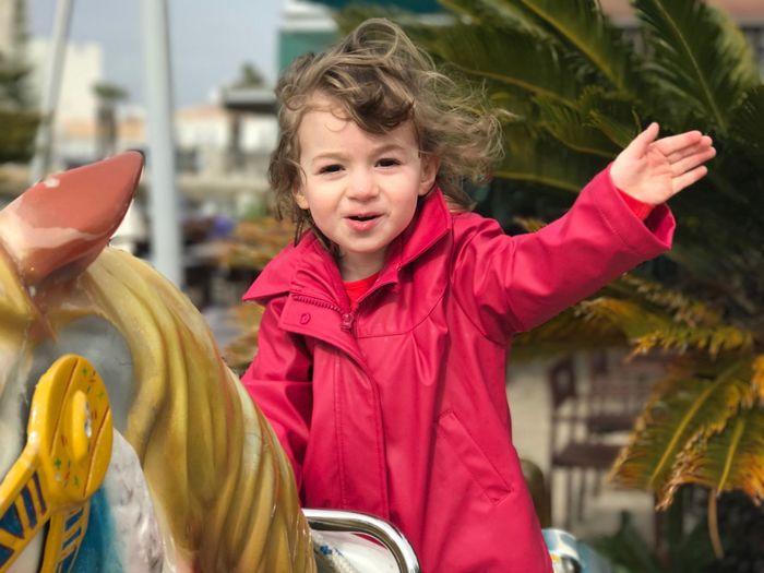 Portrait Of Cute Girl Waving Hand While Enjoying Carousel Horse Ride At Amusement Park