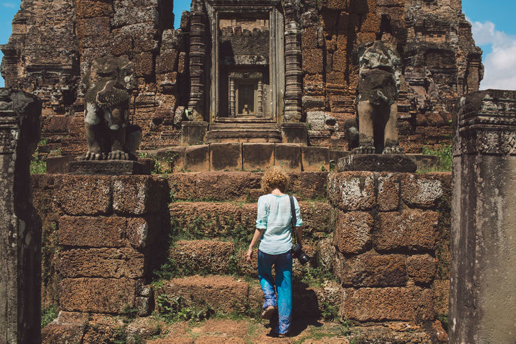 Rear view of woman standing at old ruined temple