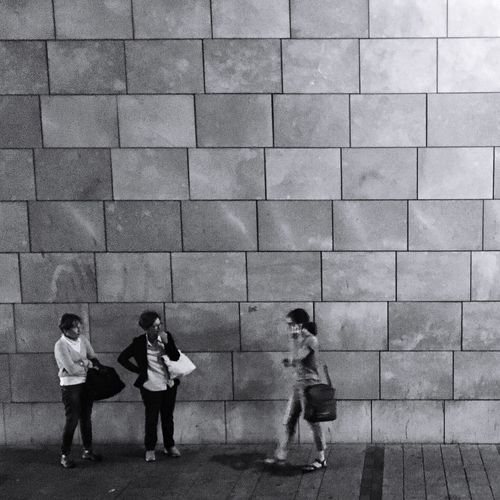 People standing on footpath against wall