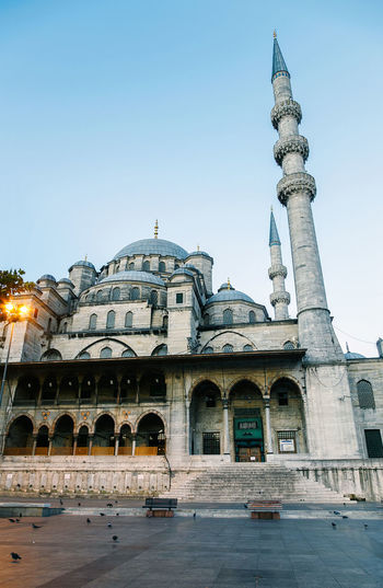 Low angle view of historic mosque in city against sky